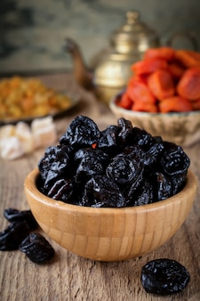 Prunes in a bamboo bowl on an old wooden. healthy dried fruit