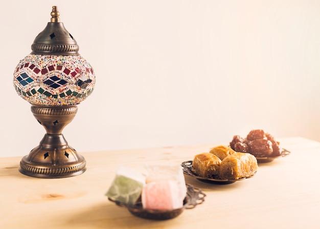 Prunes near baklava and turkish delights on saucers