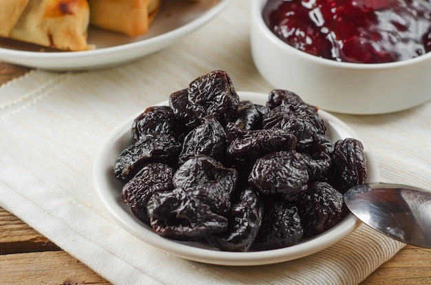 Prunes on small plate with jam from the plums on wooden table
