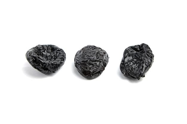 Чернослив три сушеные сливы, изолированные на белом наборе сухофруктов