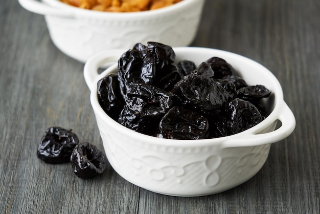 Prunes in a white bowl on a wooden table