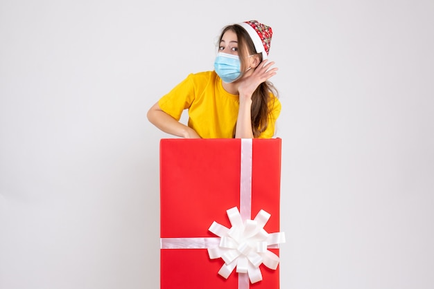 Prying girl with santa hat listening something standing behind big christmas gift on white