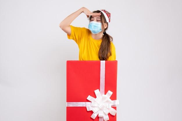 화이트에 큰 크리스마스 선물 뒤에 서있는 산타 모자와 함께 우는 소녀