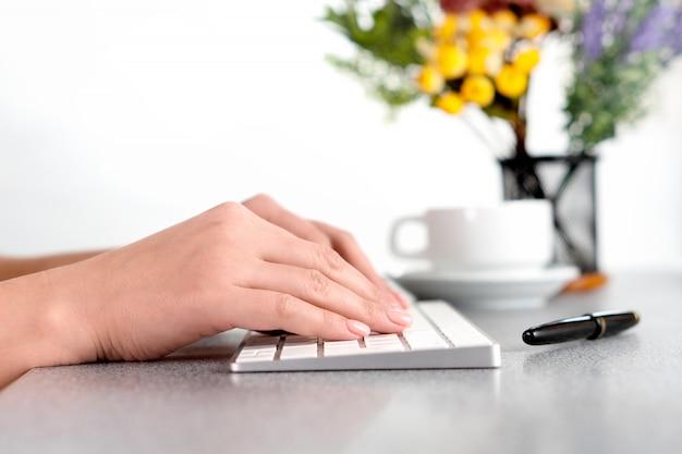 オフィスのテーブルで、psキーボードで入力する女性の手のクローズアップビデオ。バックグラウンドでの花。