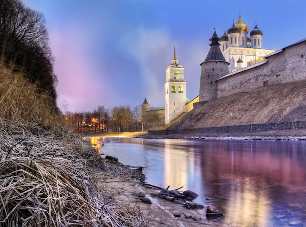 The pskov kremlin on the banks of the pskova river and frosty grass on a pink winter evening