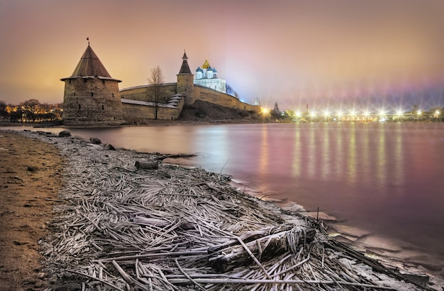 Pskov kremlin on the banks of the velikaya river and frosty grass on a winter evening