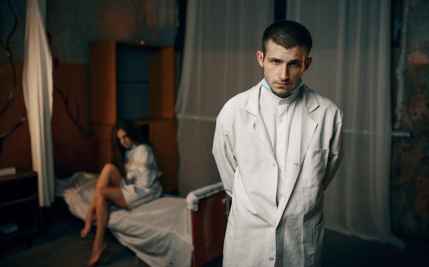 Психиатр и сумасшедшая пациентка в смирительной рубашке, психбольница. женщина в смирительной рубашке проходит лечение в клинике для душевнобольных