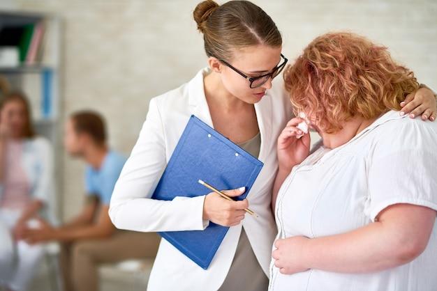 精神科医が泣いている若い女性を慰める