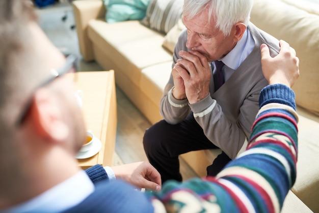 Psychiatrist consoling elderly patient