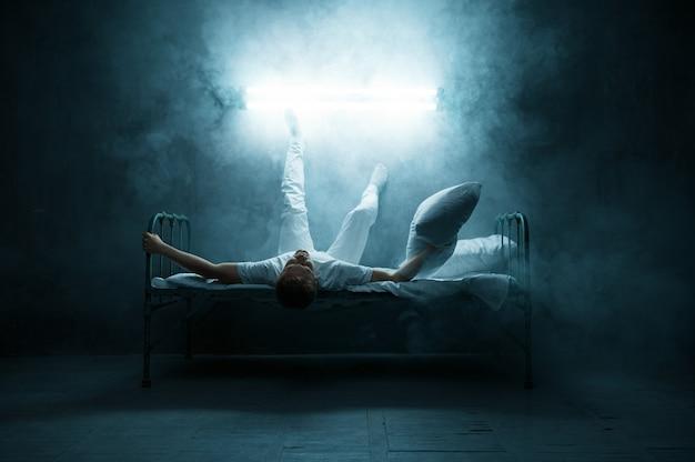 Психо-мужчина, лежащий в постели, ужас бессонницы, темная комната .. психоделический мужчина, имеющий проблемы каждую ночь, депрессия и стресс, грусть, психиатрическая больница