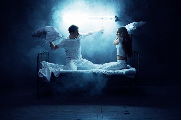 Psycho man and woman fights on pillows in bed, dark room.. psychedelic person having problems every night, depression and stress, sadness, psychiatry hospital