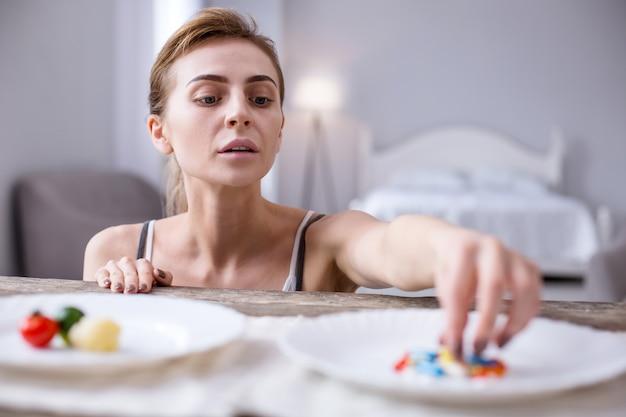 Психологическая зависимость. подавленная молодая женщина выбирает таблетки, будучи психологически зависимой от них
