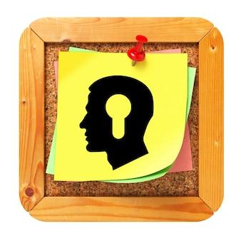 Психологическая концепция - профиль головы со значком замочной скважины на желтой наклейке на пробковой доске для сообщений.