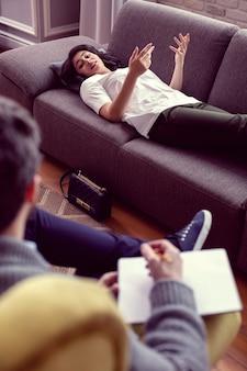 心理的な助け。ソファに横になっている間、医者に彼女の問題を説明する楽しい若い女性