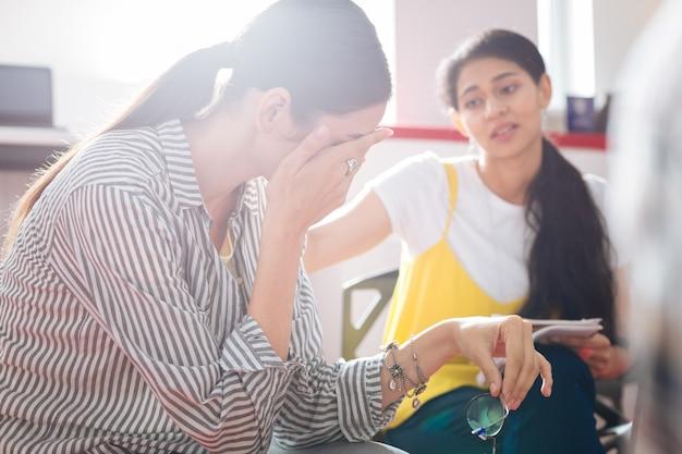 心理的な助け。プロの信頼できる心理学者が彼女を見ている間、不幸なストレスを感じた女性が泣いて顔を隠している