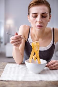 심리적 문제. 다이어트에 집착하면서 그릇을 들여다 보는 슬픈 쾌활한 여자