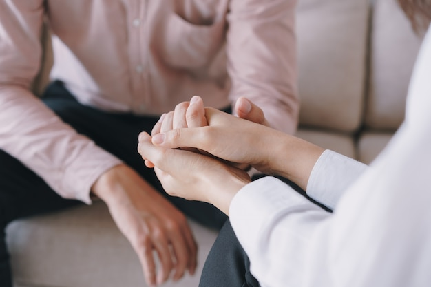 Psychological women comforting and holding a male hand while sitting on the sofa