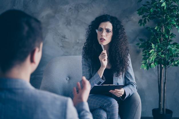 Психолог эксперт девушка сидит в кресле, слушает клиента на сером фоне стены