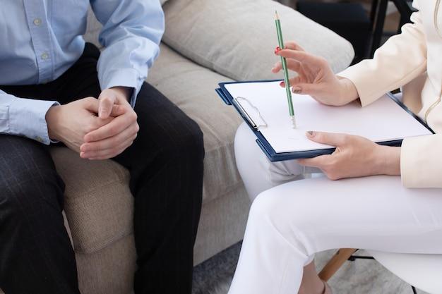 心理学者が患者とプライベートの診察室でセッションを行っている。