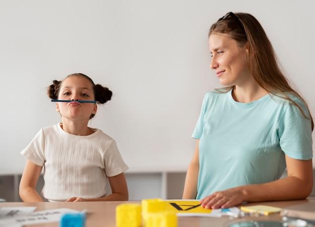 언어 치료에서 소녀를 돕는 심리학자
