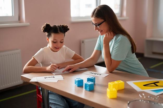 Psicologo che aiuta una bambina nella logopedia al chiuso