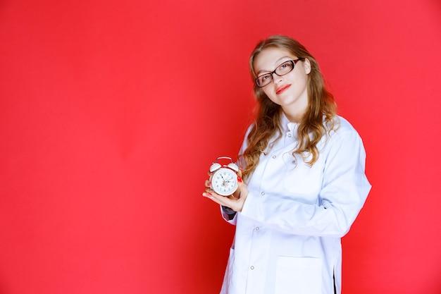 正しい睡眠時間を指す目覚まし時計を持っている心理学者。