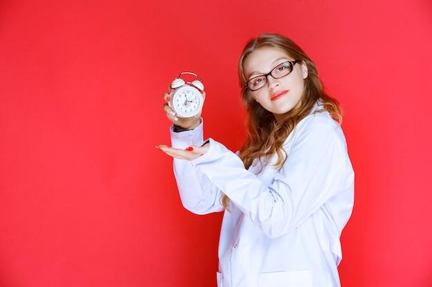 올바른 수면 시간을 가리키는 알람 시계를 들고 심리학자.