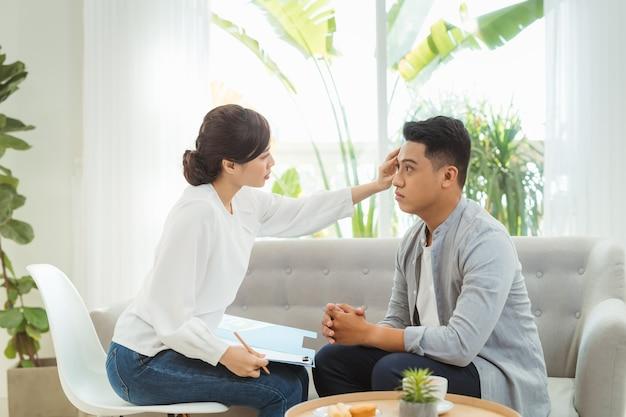 心理学者は患者の話を聞き、メモ、メンタルヘルス、カウンセリングの概念を書き留めます