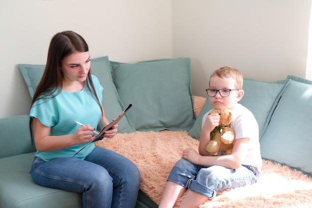 Психолог слушает маленького ребенка во время сеанса терапии. мальчик дошкольного возраста спокойно чувствует себя в кабинете терапевта, делится своими мыслями и проблемами.