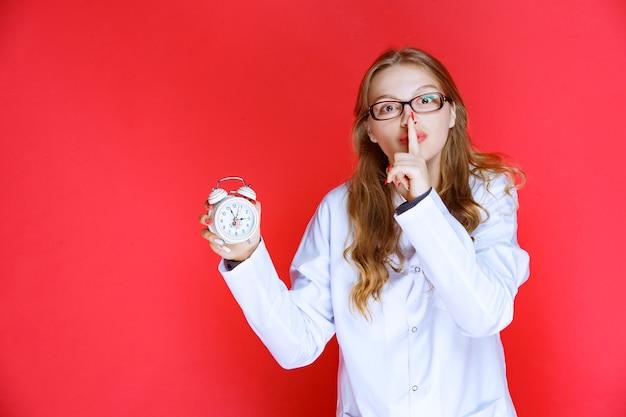 目覚まし時計を見せて沈黙を求める心理学者。