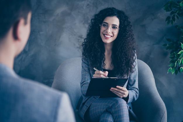 Девушка-психолог-специалист сидит в кресле, слушает, как клиент делает заметки на бетонной стене