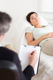 悲しい女性患者と話す心理学者
