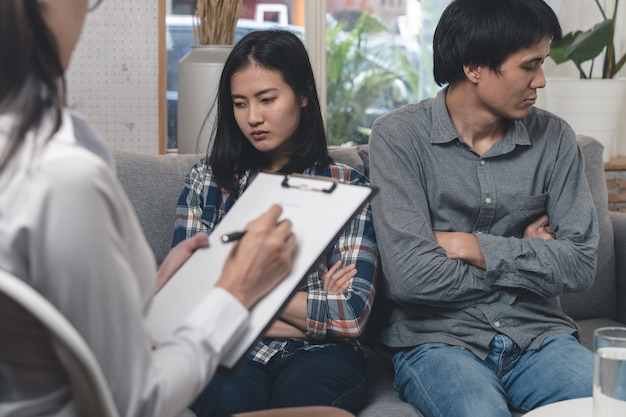 Psychologist talking with asian married couple at clinic.