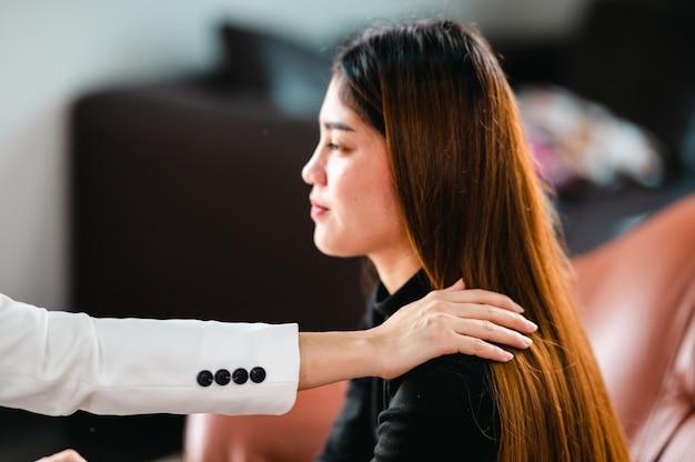 심리학자는 어깨를 만지고 여성 환자의 문제를 이해하는 데 도움을 줍니다.