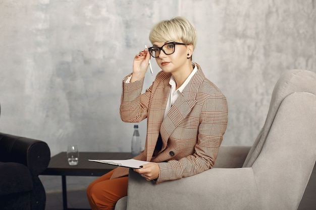 Psychologist with glasses sitting on a chair at the office