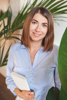 Psychologist woman with book in office with tropical plants