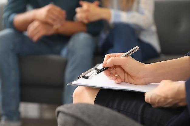 Психолог, работающий с молодой парой в офисе, крупным планом