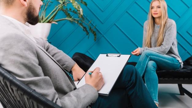 心理学者の彼のメスの患者との会談中にペンでクリップボードにメモを書く