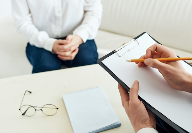 Психолог пишет на бумаге пациента коммуникативной терапии