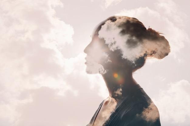 심리학과 여성 정신 건강, 날씨 의존적 개념. 다중 노출 구름과 여성의 머리 실루엣에 태양.