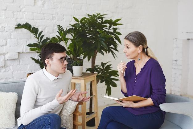 심리학, 치료, 정신과, 정신 건강 및 상담 개념. 직장에서 자신의 문제에 대해 중년 여성 상담사에게 말하는 안경에 긴장된 자의식이 강한 젊은 남성의 솔직한 샷
