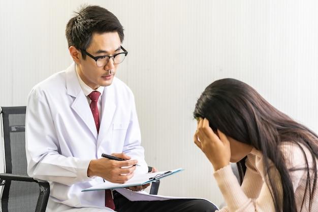 落ち込んでいるアジアの女性と一緒に働く忍耐の家を訪問する心理療法士の医者
