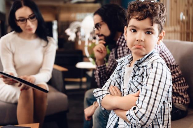 심리 치료사는 여자입니다. 아들은 화를 내고 불만을 나타냅니다.