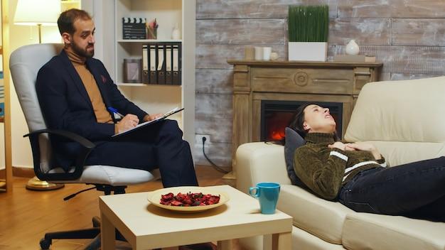 不幸な女性が彼女の不幸な関係について話している間にメモを取る心理療法士。