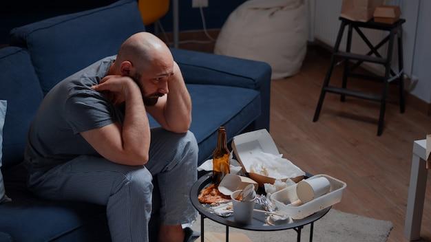 精神病の一人で落ち込んでいる男がソファに座ってがっかりしている