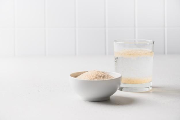 차전자피와 흰색 탁자에 있는 장을 위한 수용성 섬유 보충제 한 잔