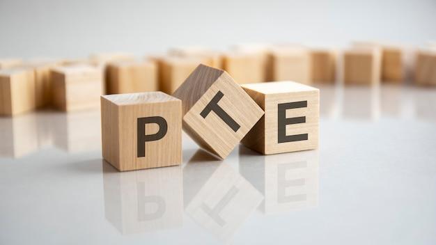 Pte-キューブ、灰色の背景での英語の頭字語概念のピアソンテスト。テーブルの鏡面での反射。セレクティブフォーカス。