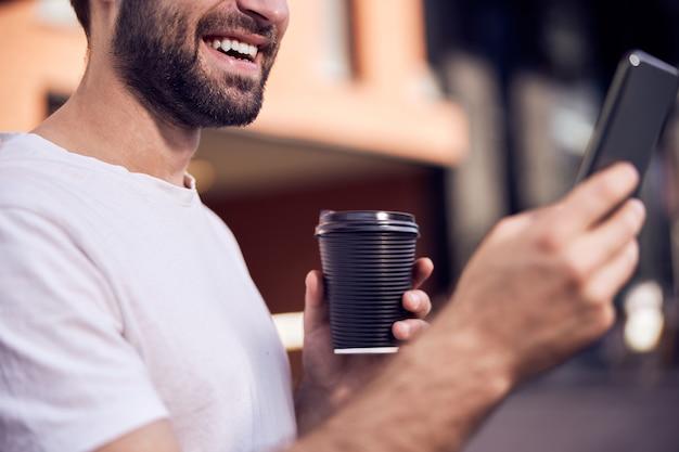 커피 들고 스마트 폰 야외 미소 남자의 ptoto를 닫습니다.