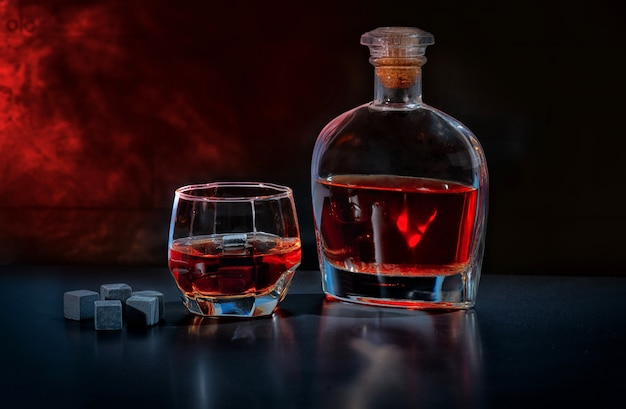 Пабный натюрморт с бренди в стакане и графине рядом с охлаждающими блоками из черного шунгита или многоразовыми кубиками льда на фоне дымной атмосферы
