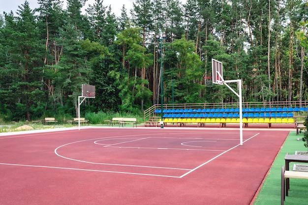 공공 농구 코트 야외입니다. 숲과 가까운 도심 외곽의 텅 빈 종합운동장.